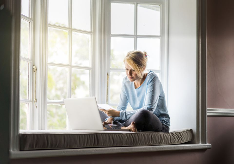A young woman using a laptop on window sill