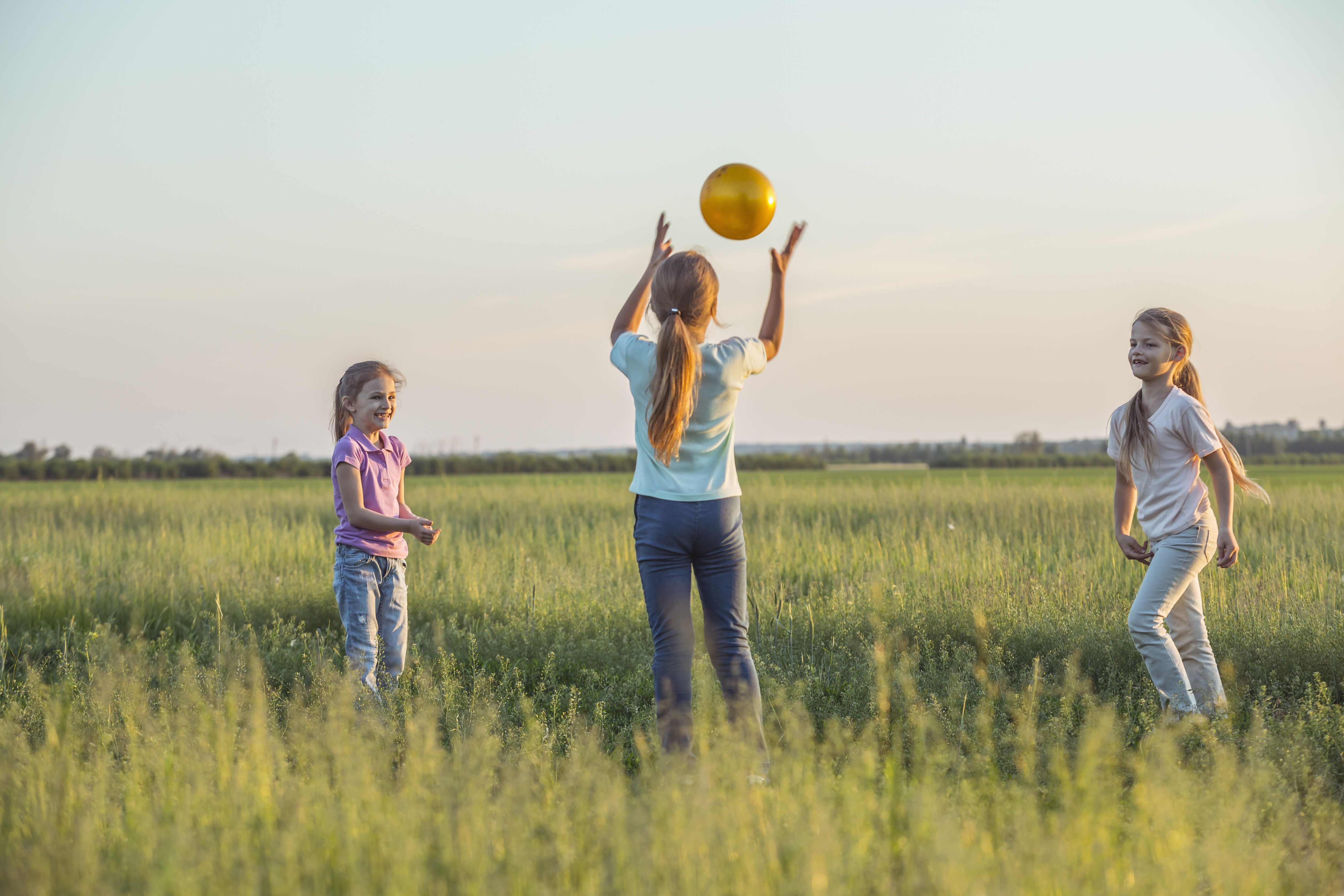 Three young girls playing catch in a sunny field in summer