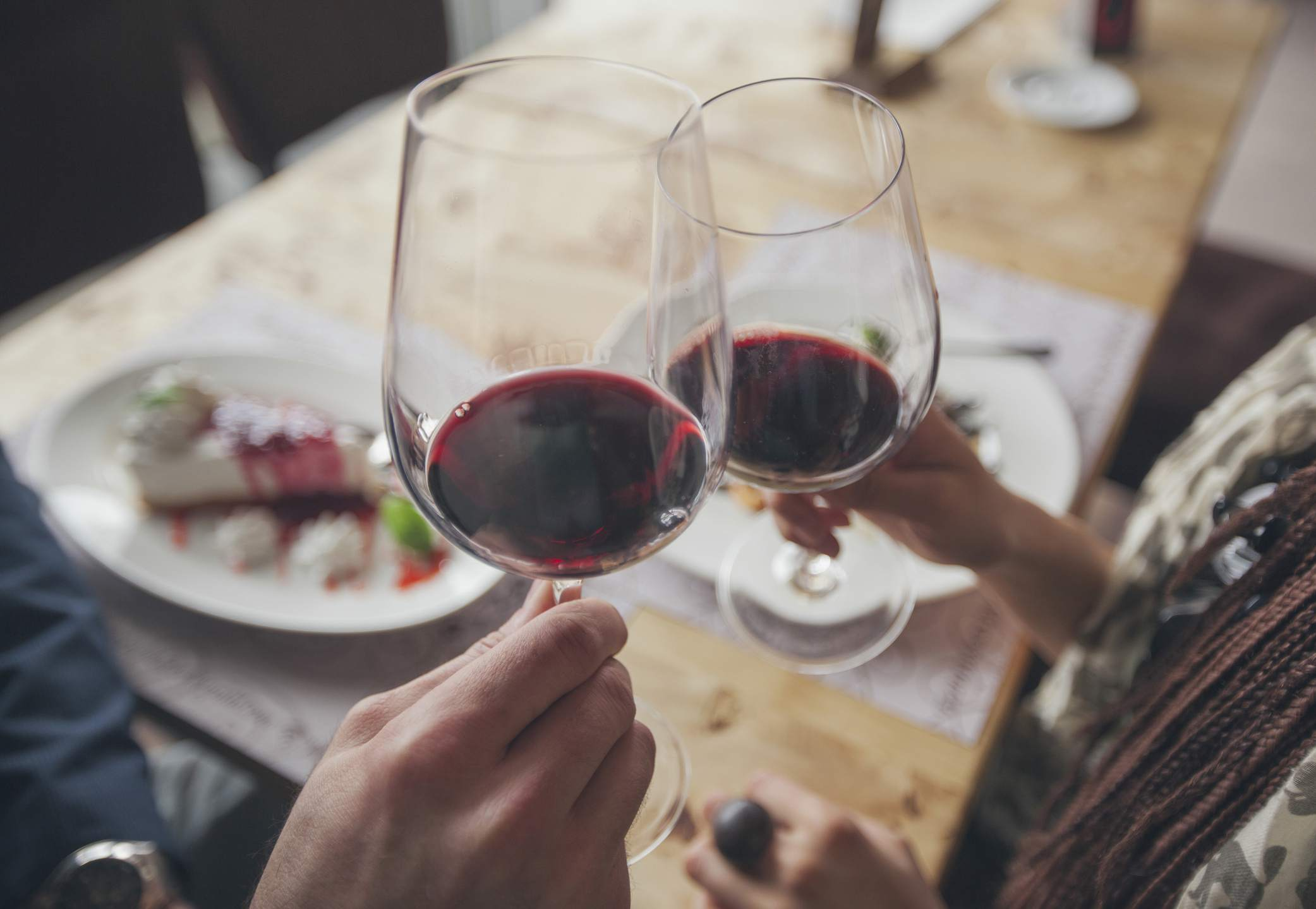 Couple toasting two glasses of red wine