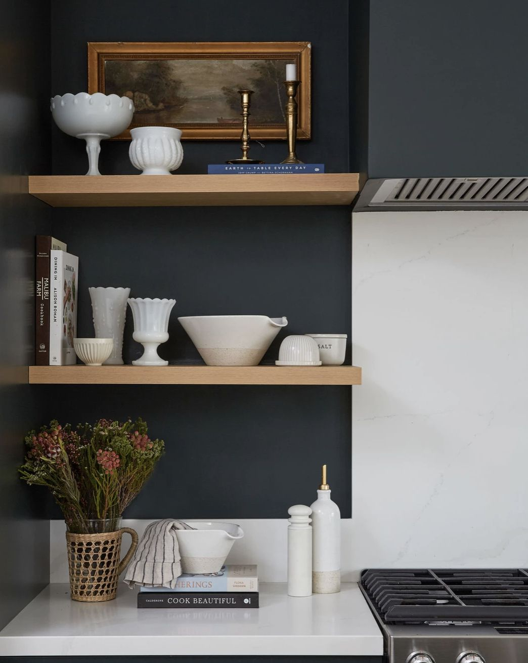 open shelving with various kitchen dishes and cookbooks