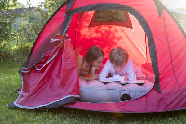 kids reading on air mattress in tent