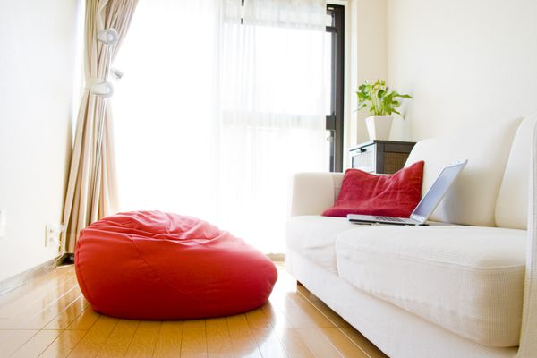 Red beanbag in contemporary living room next to white couch with red pillow and laptop
