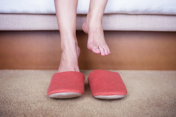 woman putting on slippers