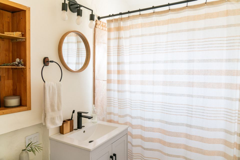 Small bathroom with small round mirror next to white and tan shower curtain