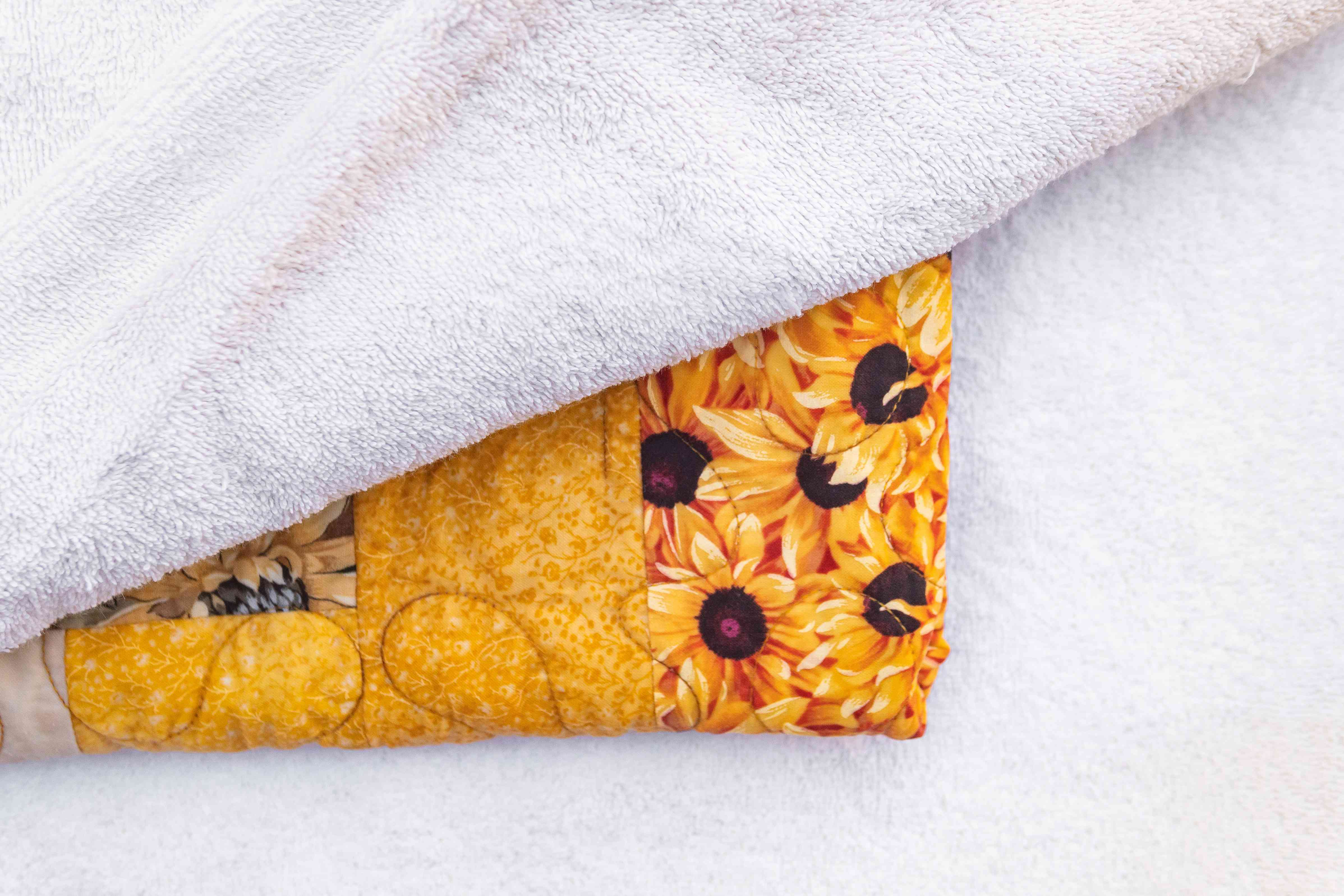 Vintage quilt covered by white towels