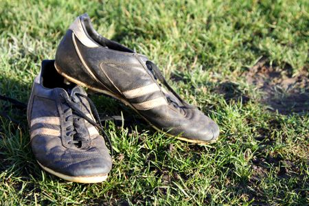 Dirty football boots on a grass pitch