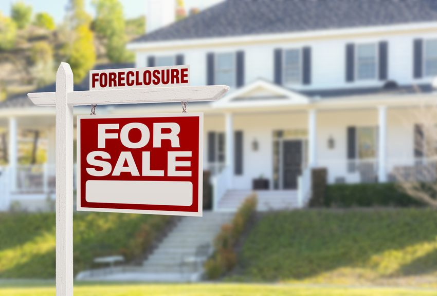 a home with a foreclosure sign in front of it