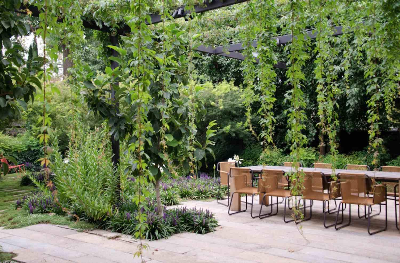Jardín de sombra con mesa y sillas. Jardín sombreado con una pasarela de piedra y un jarrón utilizados como punto focal