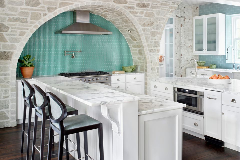 White kitchen with marble countertops, stone arch, and a bi-level countertop