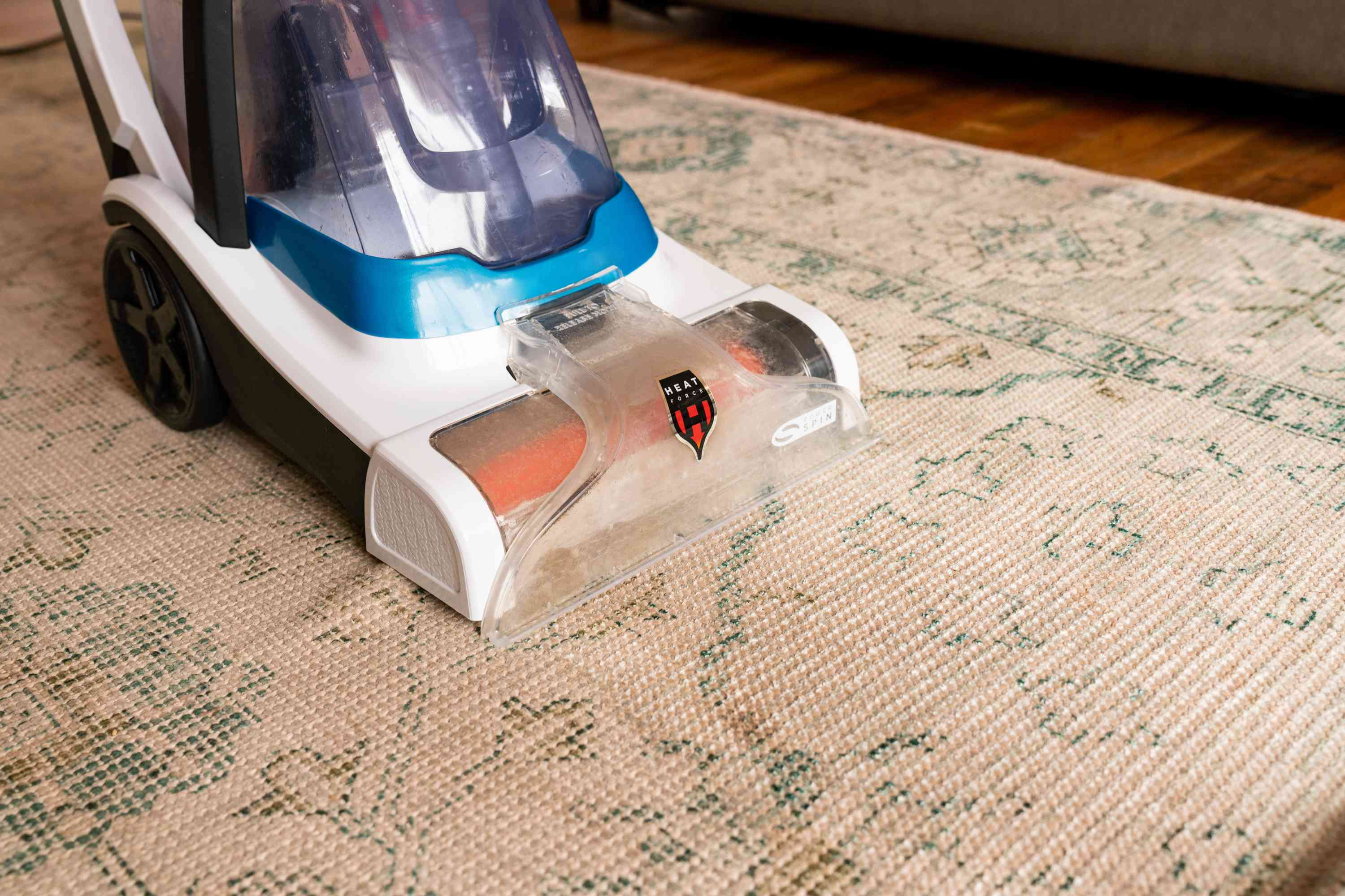 White and blue steam cleaner passing over old tan rug with hit water extraction