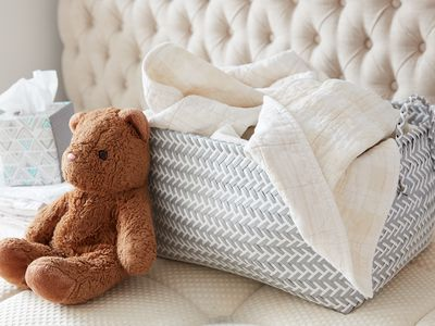 laundry basket, tissues, and teddy bear on top of a mattress