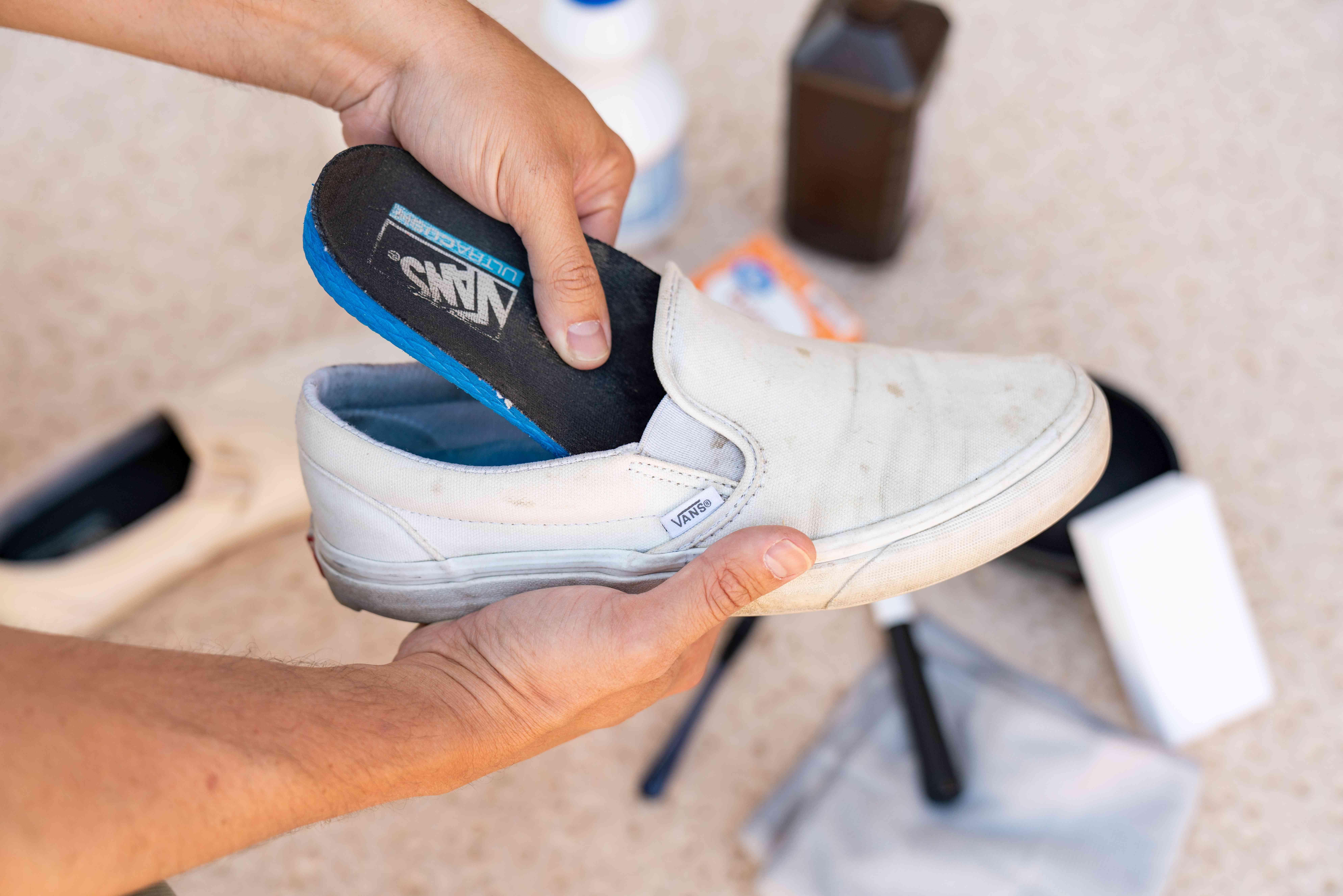 Insoles being removed from dirty white vans