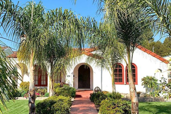 Mission style home with palm trees outside
