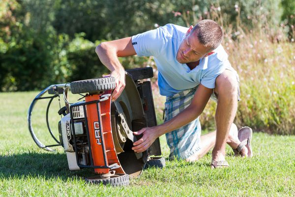 Man inspecting deck and blade of lawn mower.