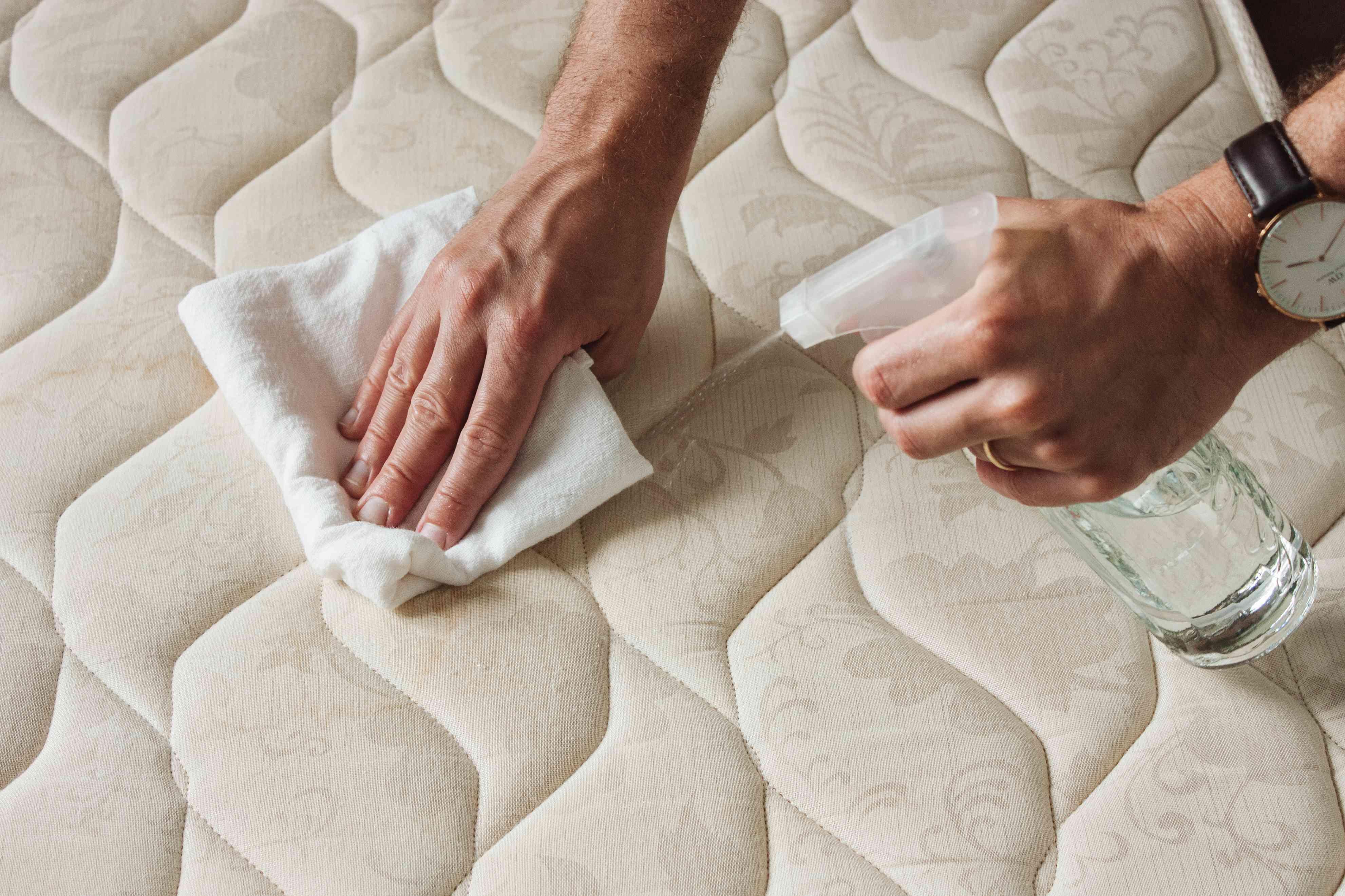 person spraying a mattress
