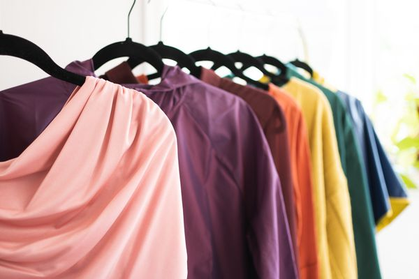 Synthetic fabric clothing hanging on black hangers with various colors