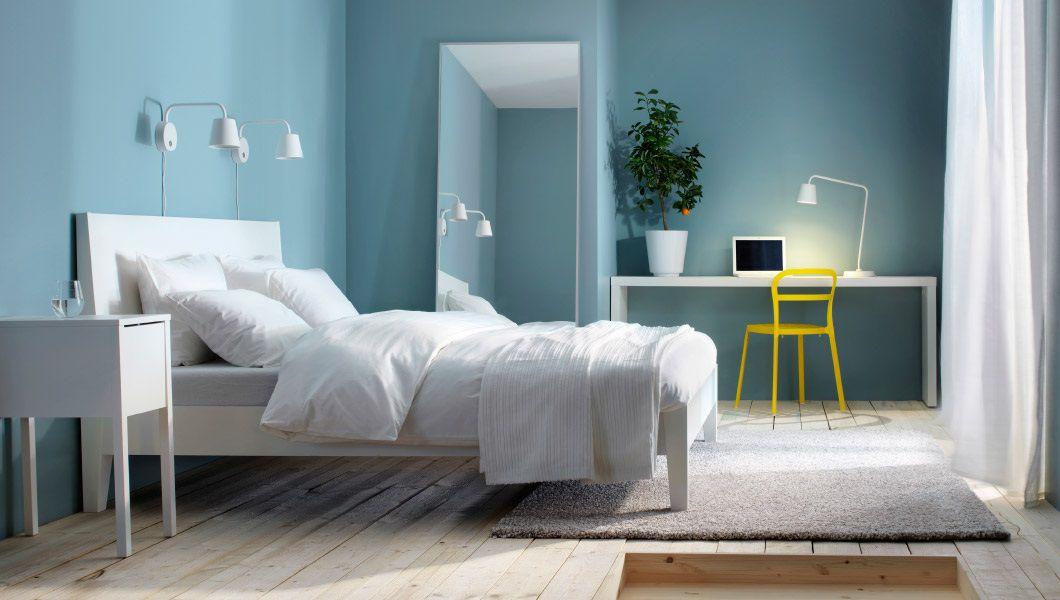 Cama blanca en una habitación azul