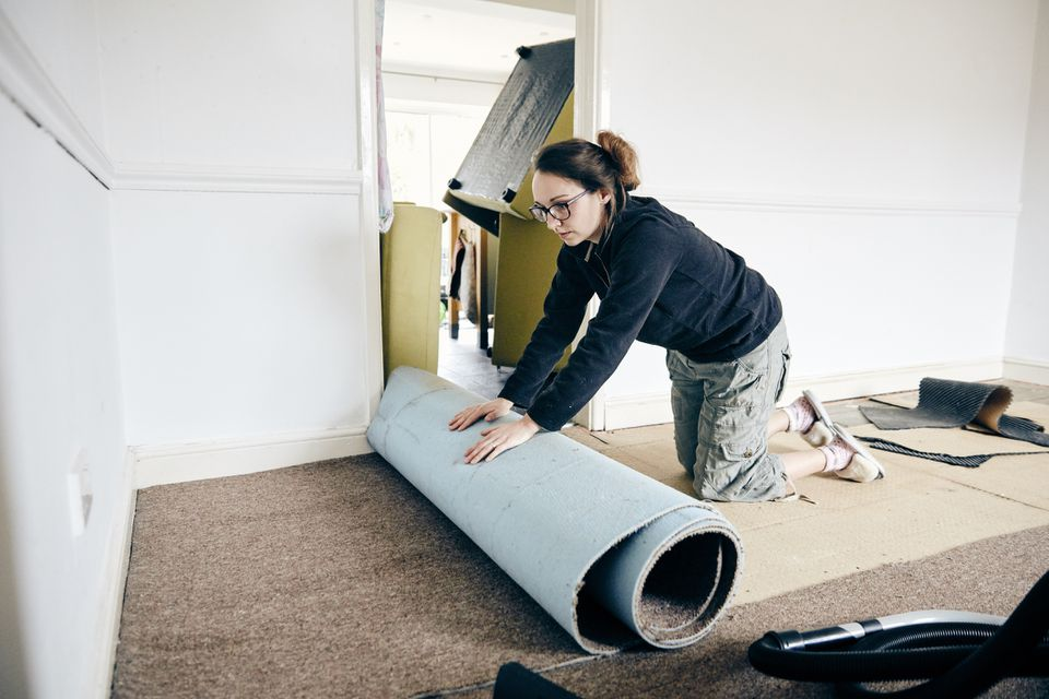 Lady removing carpet from a room