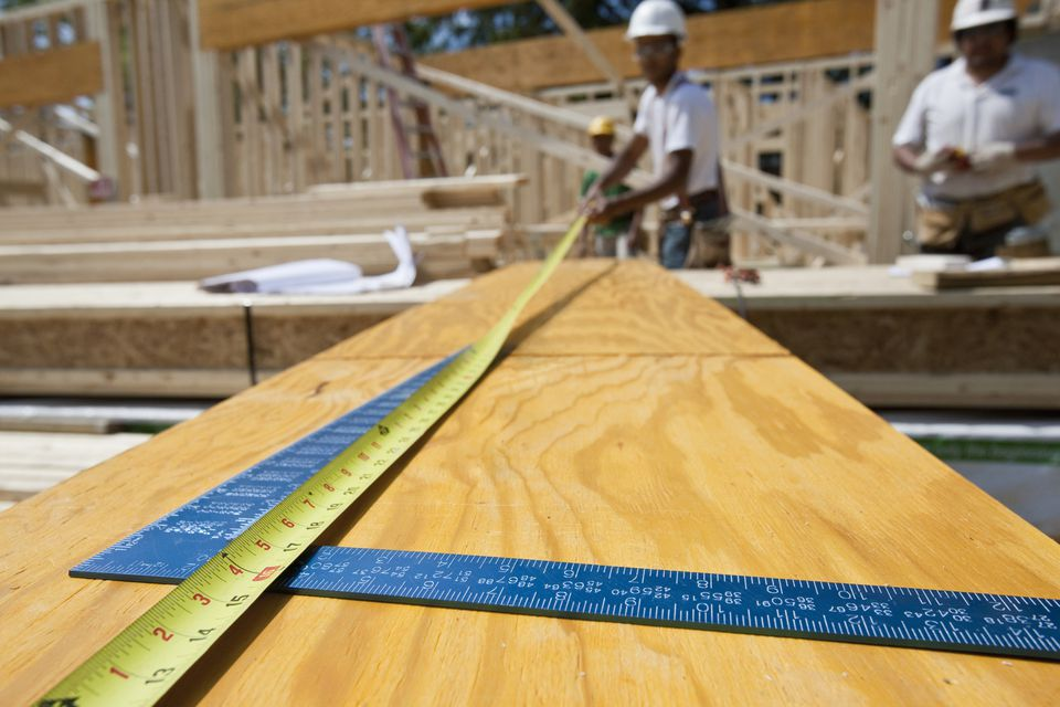 Worker measuring Laminated Veneer Lumber or LVL with a measuring tape and L-ruler.