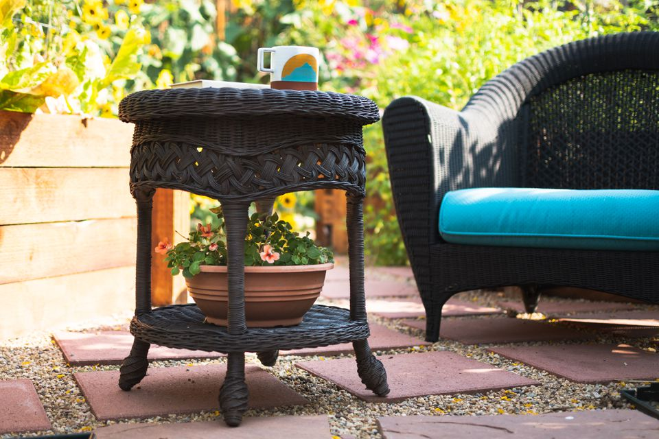 Outdoor wicker furniture painted black and decorated with potted plant, coffee mug and cushion