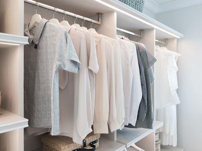 Modern interior wardrobe with shirt and dress in shelf.