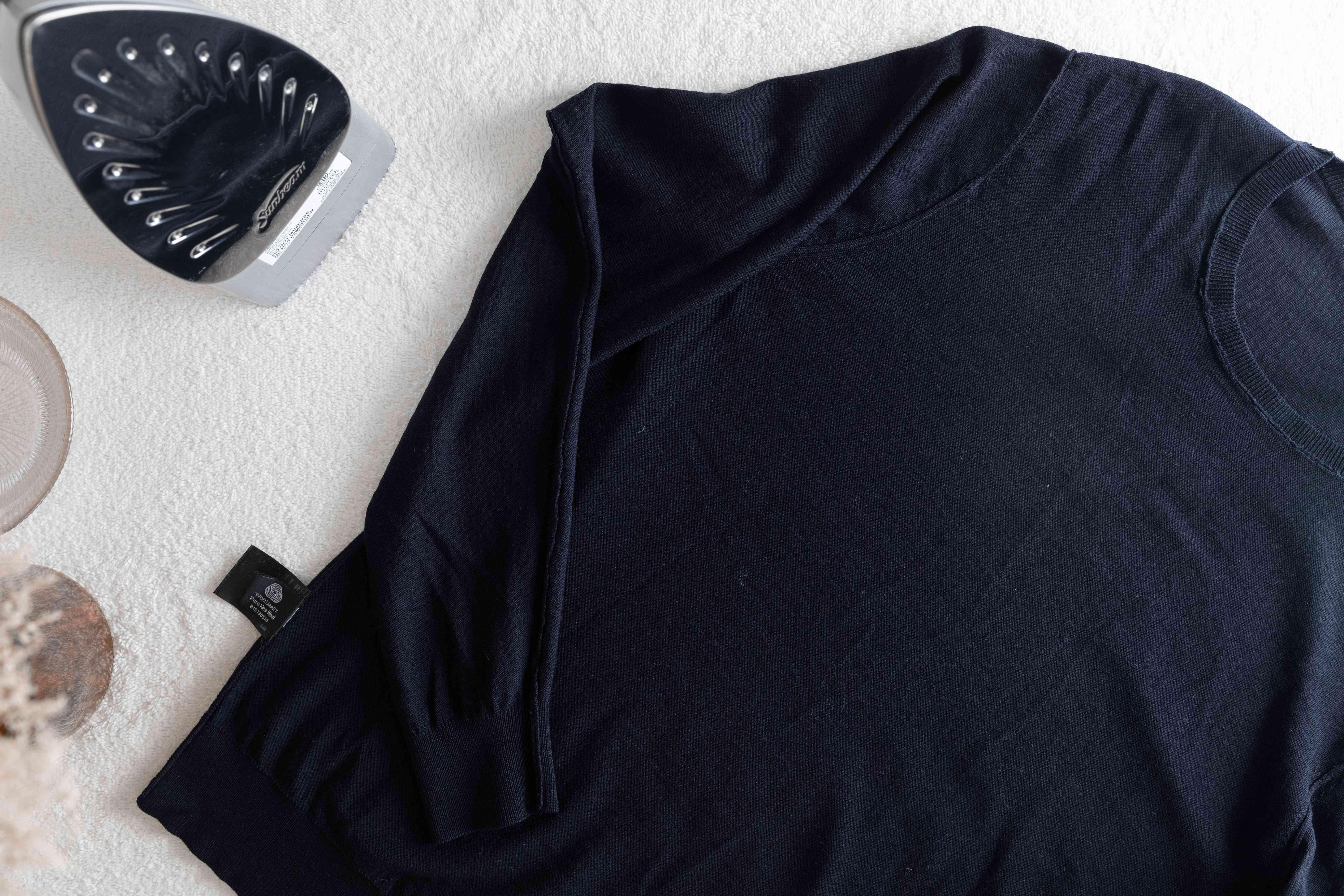 An inside-out sweater next to an iron
