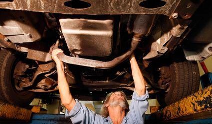 A mechanic replaces a stolen catalytic converter
