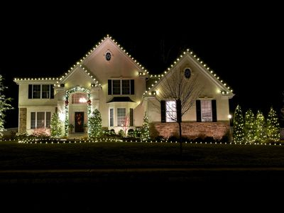 white lights along the eaves of three front gables of a white house -- a horizontal row of white lights at the ground level complements the arrangement