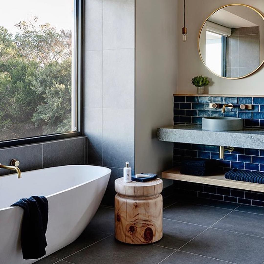 Bathroom with large white tub and cement sink