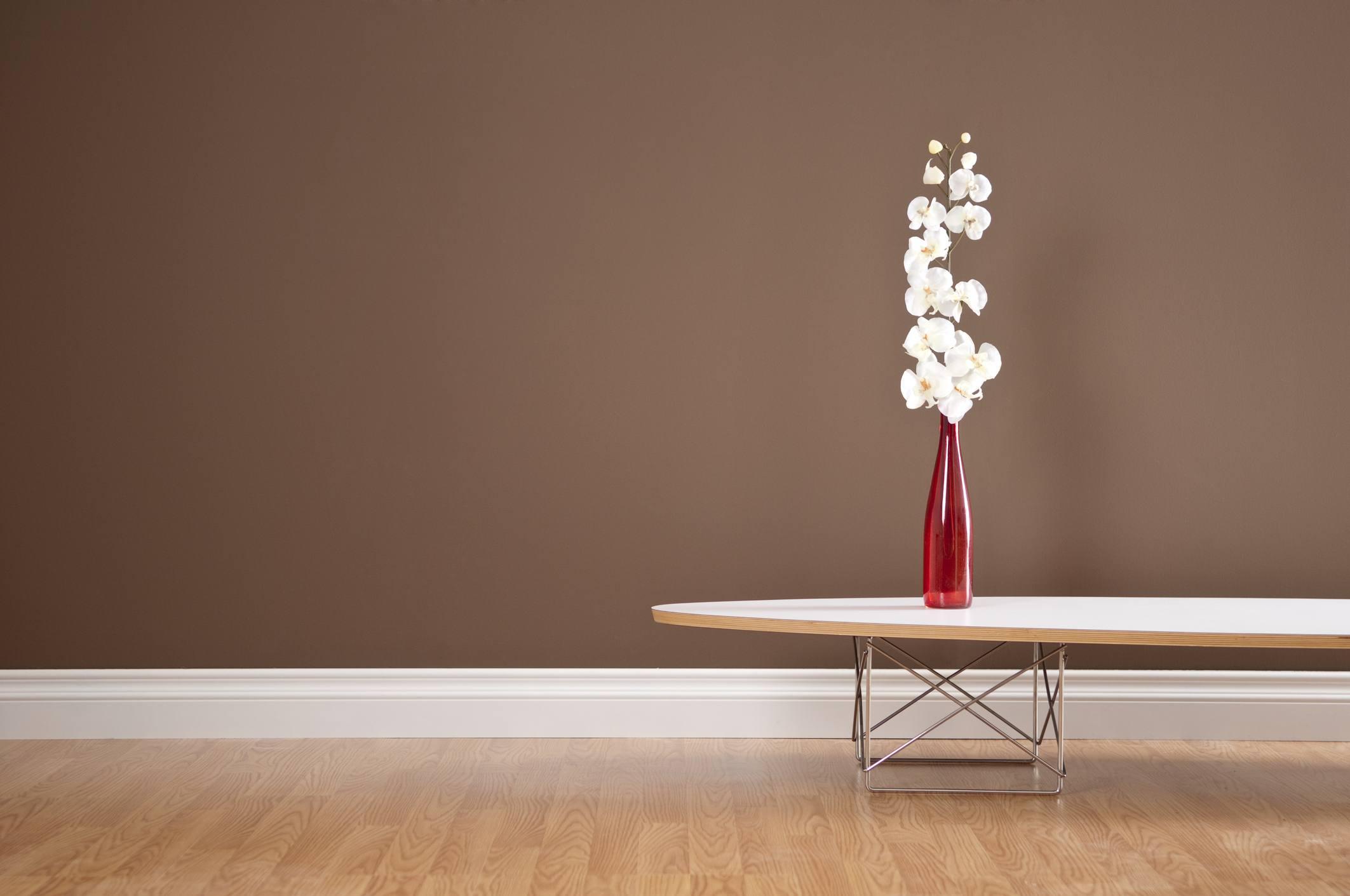 Sala de estar con mesa de centro moderna con flores en un jarrón rojo