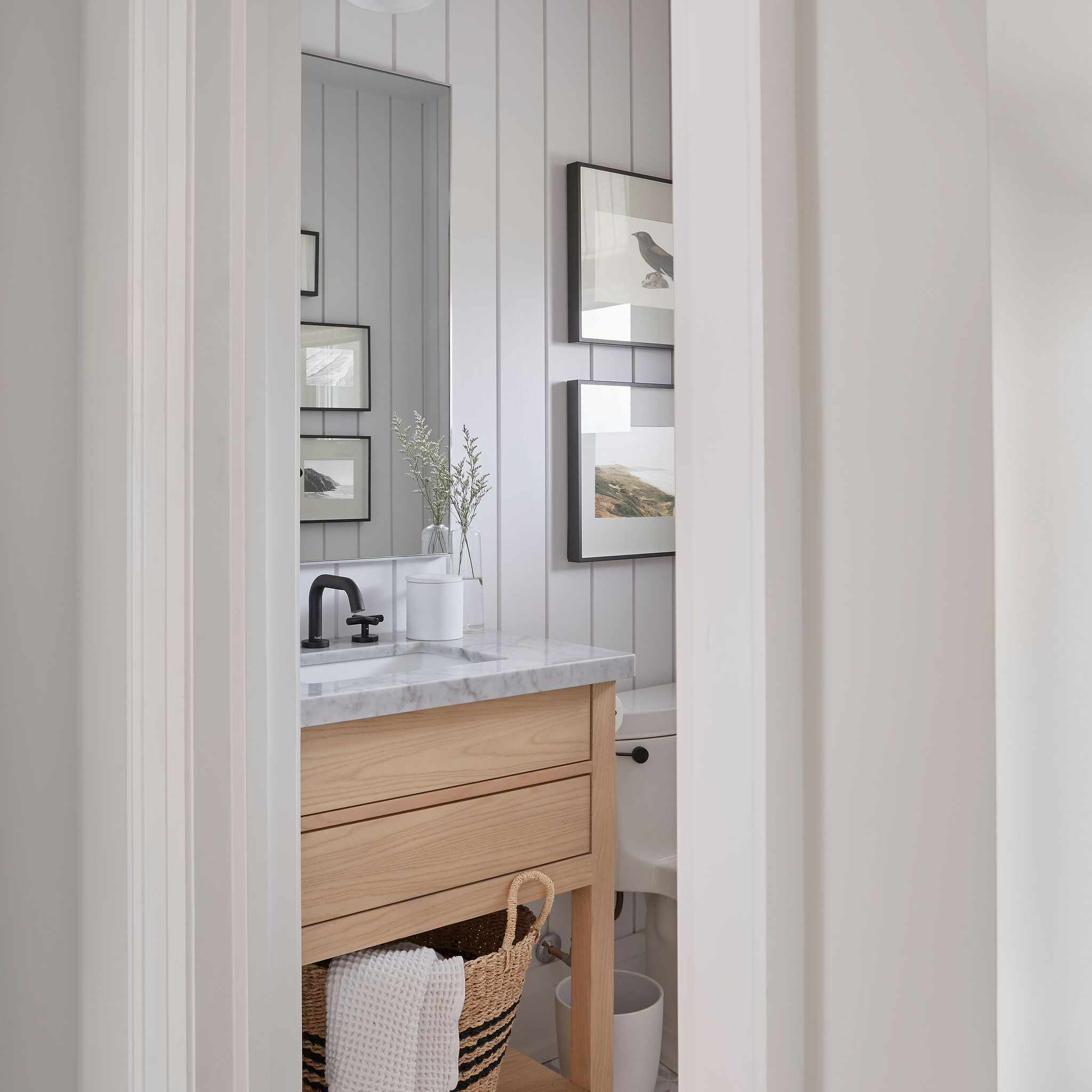 Lovely white bathroom with natural wood cabinetry and marble countertop