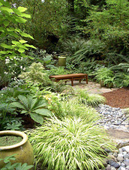 Jardín de sombra con rocas y banco