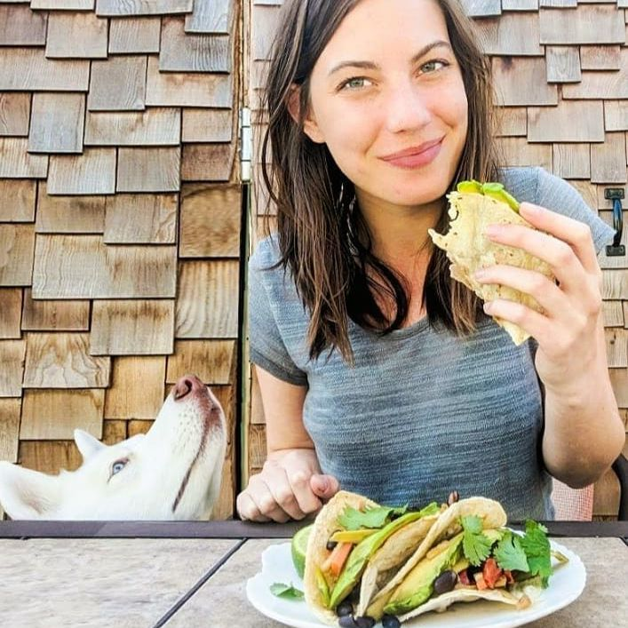person eating vegetable tacos with a dog sniffing at them