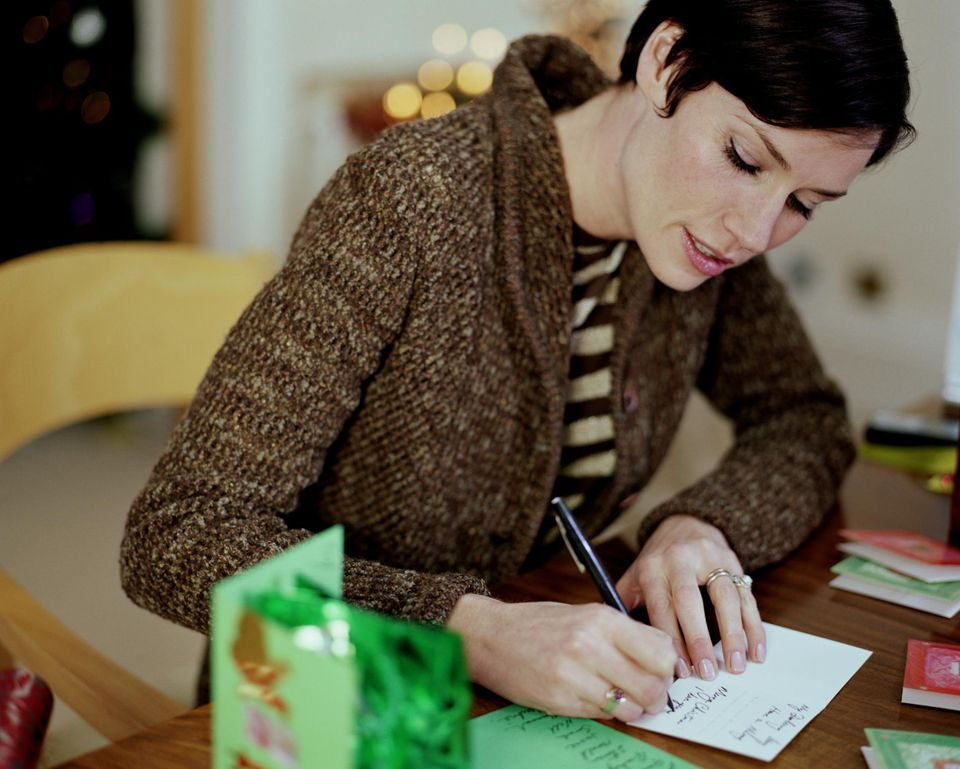 Woman sitting at table writing Christmas cards.