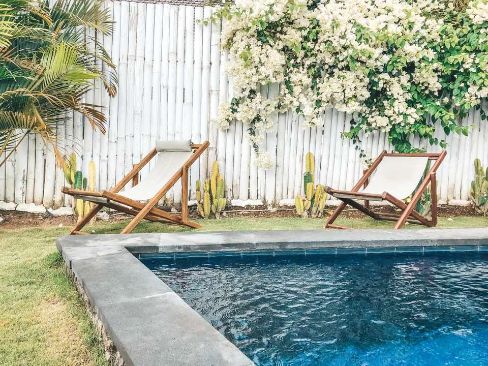 A white bamboo fence around a backyard pool.