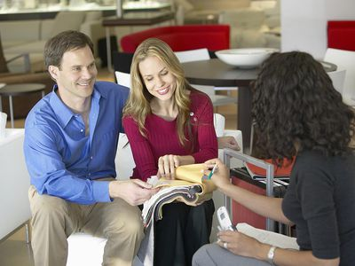 A couple talking with a salesperson about furniture
