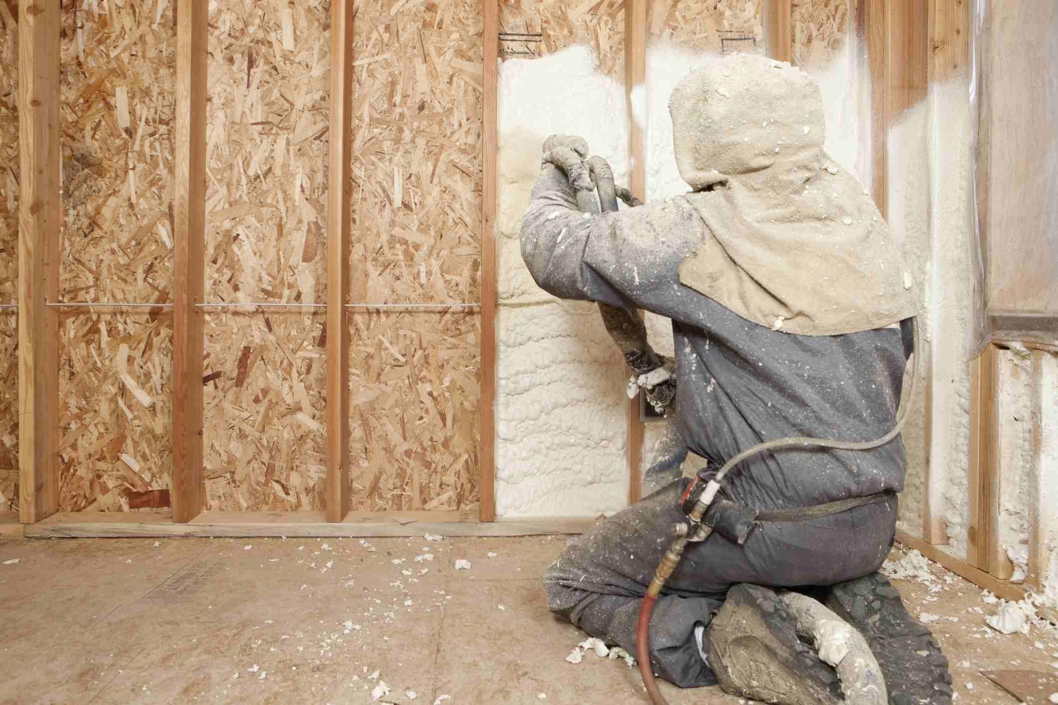 Spraying foam insulation into the wall