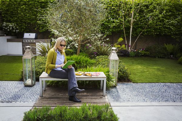 Woman sitting on a bench in a garden, drawing flowers in a sketchbook.