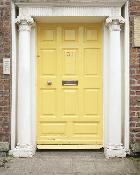 Una puerta amarilla en una casa con columnas neoclásicas