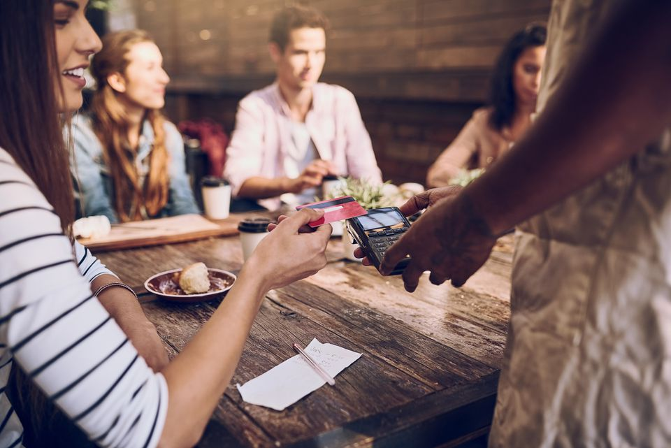 Young people at a restaurant where a woman is paying by credit card