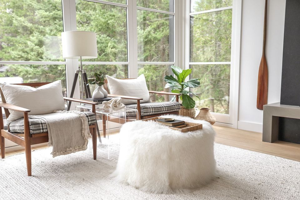 Small living room with wall to ceiling windows, two chairs and a coffee table with white fur covering