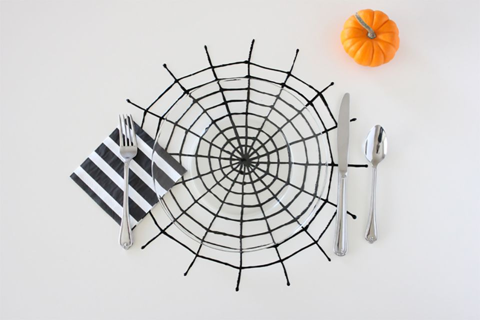 A black spiderweb with silverware and a pumpkin