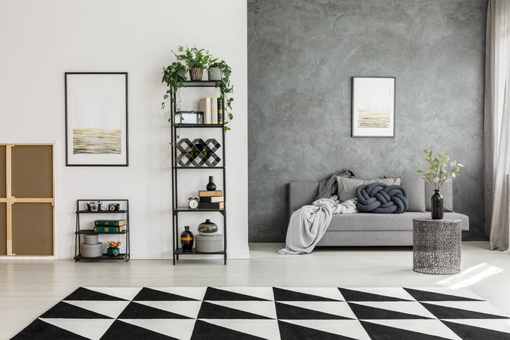 Black and white living with gray walls and couch with black-and-white rug.room