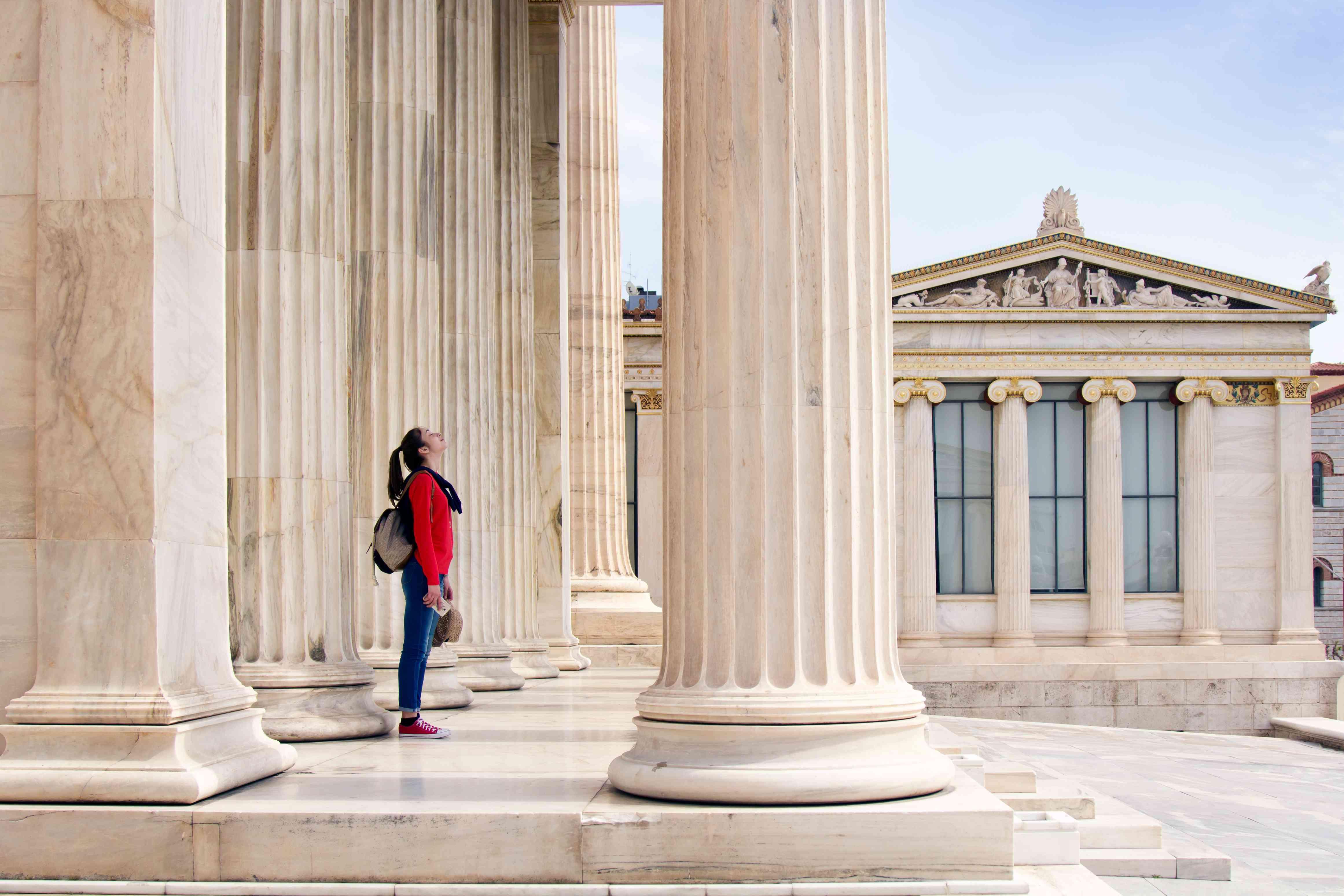 Una niña mira hacia el techo, debajo de las columnas de la Academia Ateniense