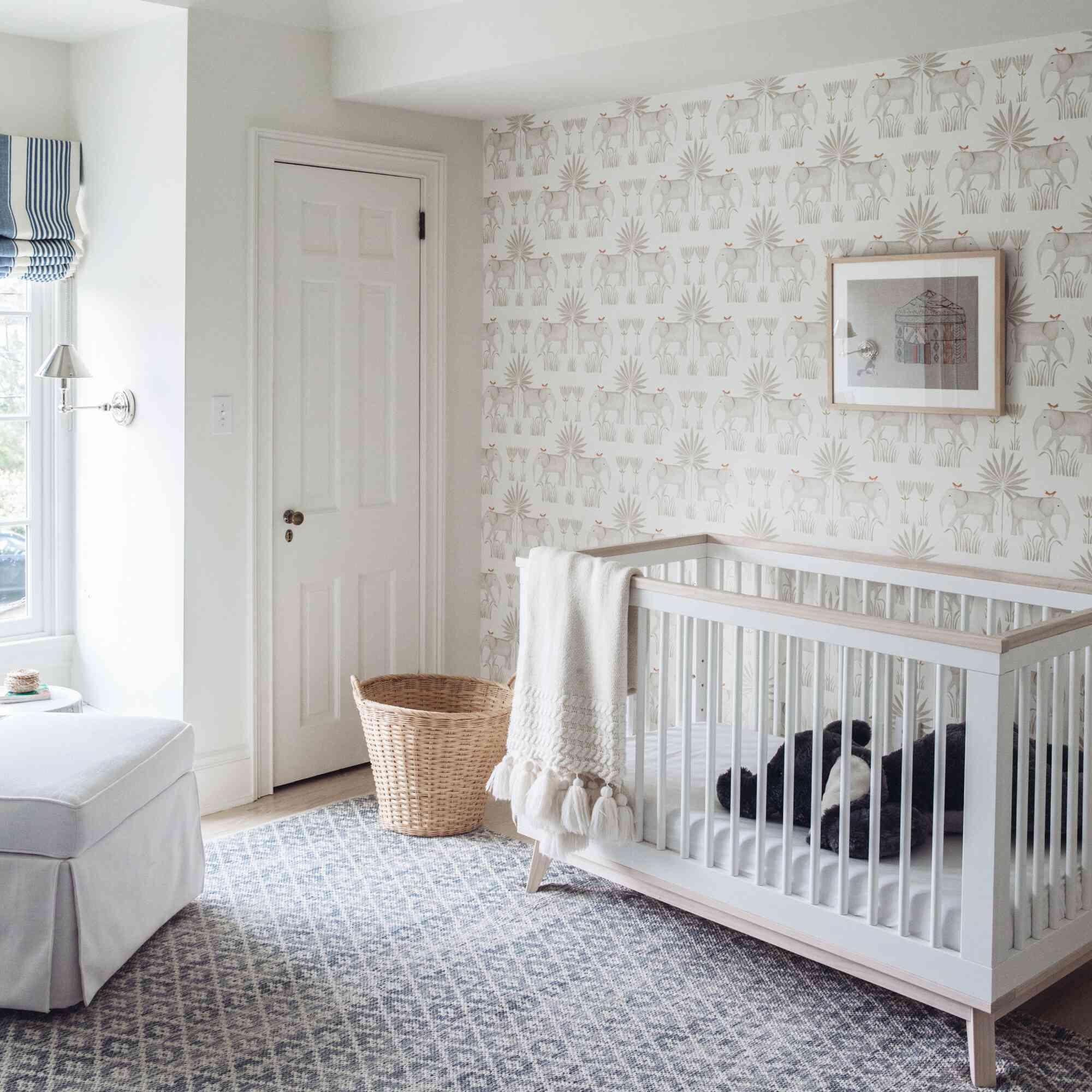 nursery with white color scheme, elephant print wallpaper, wicker basket between crib and closet door