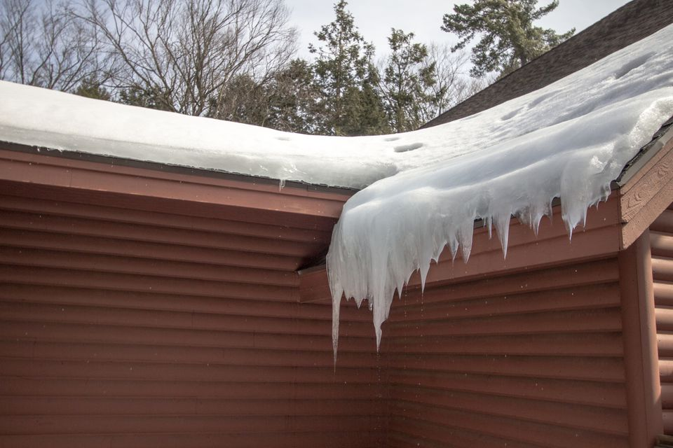 Icicles Hang From Ice Dam On Home Roof With Water Dripping