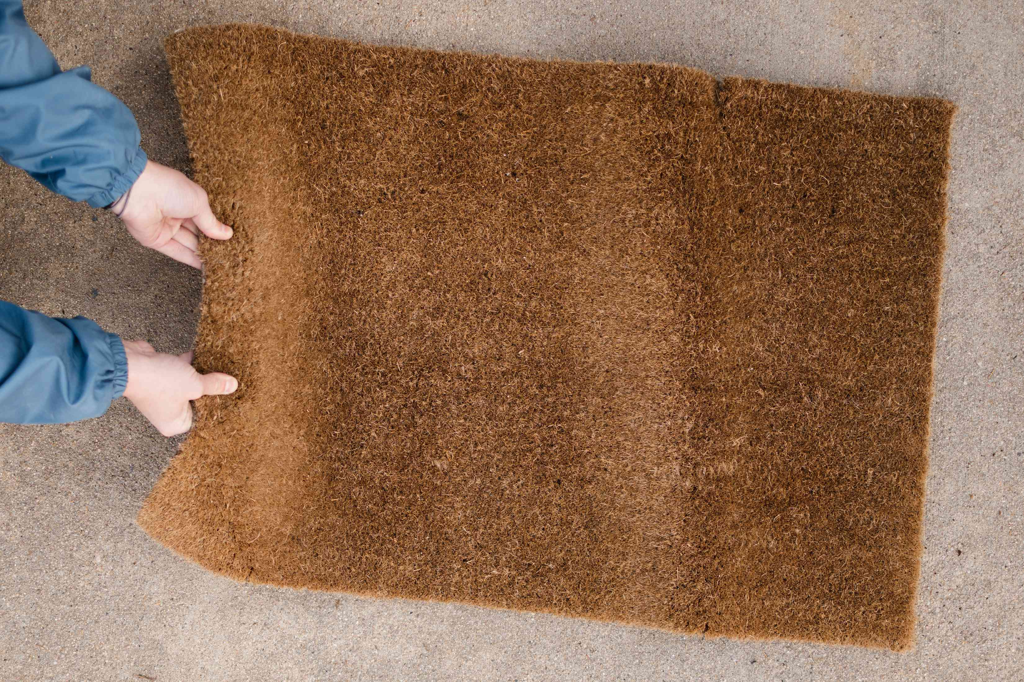 Brown doormat being shaked by hand to remove dirt