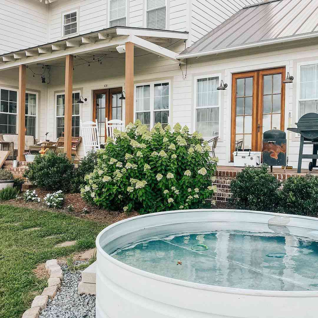 A white stock tank pool in a farmhouse-style backyard.