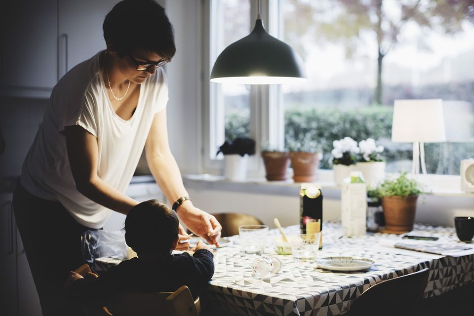 Mid adult woman with baby girl at dining table