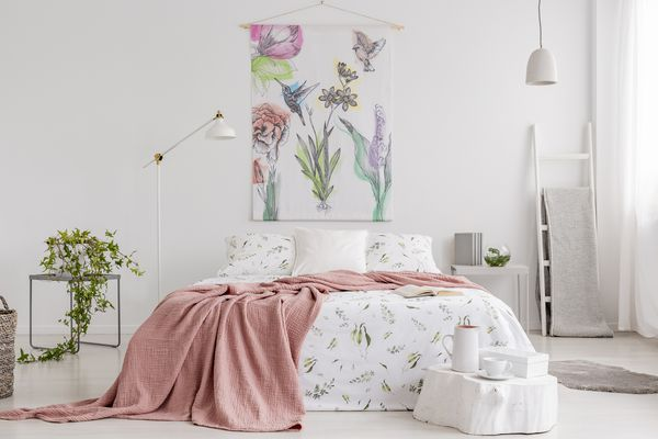 Peach blanket and white with green pattern linen on bed in a natural bright bedroom interior. Tapestry with colorful flowers and hummingbirds on the back wall.